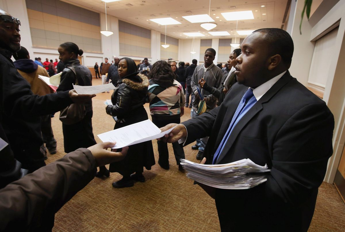 Cory Thames, with the city of Chicago human resources department, collects resumes from Job seekers as they enter a job fair being held at Kennedy-King College and hosted by the city of Chicago on November 9, 2012 in Chicago, Illinois. Thousands of people waited in line beginning at 3AM for the job fair which did not open the doors until 9AM. When the doors opened the line was about a half-mile long.  (Photo by Scott Olson/Getty Images)
