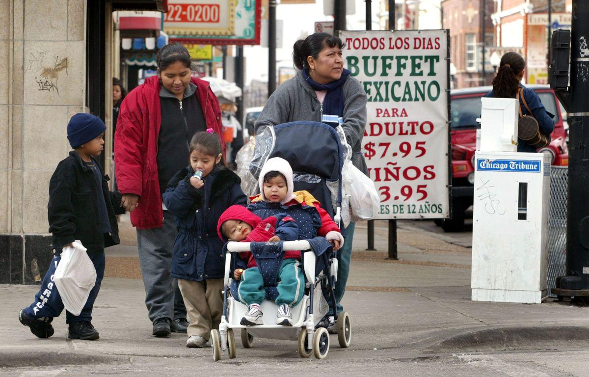 Una familia de mexicanos en las calles de Chicago. Según un estudio reciente, los hispanos han tenido menos probabilidades que los blancos de recibir dinero de estímulo económico. (Foto por Tim Boyle/Getty Images)